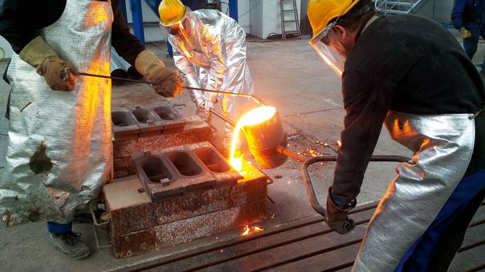 Employees pour molten metal into molds